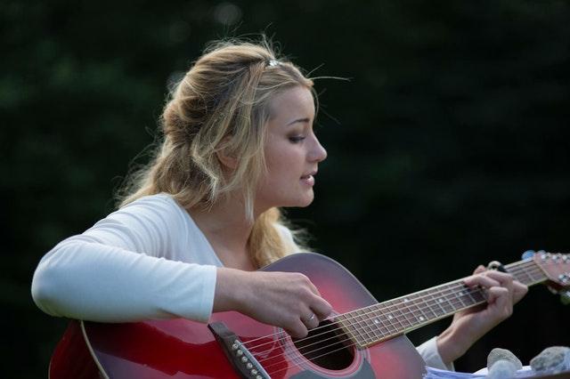 mladá žena hraje na kytaru